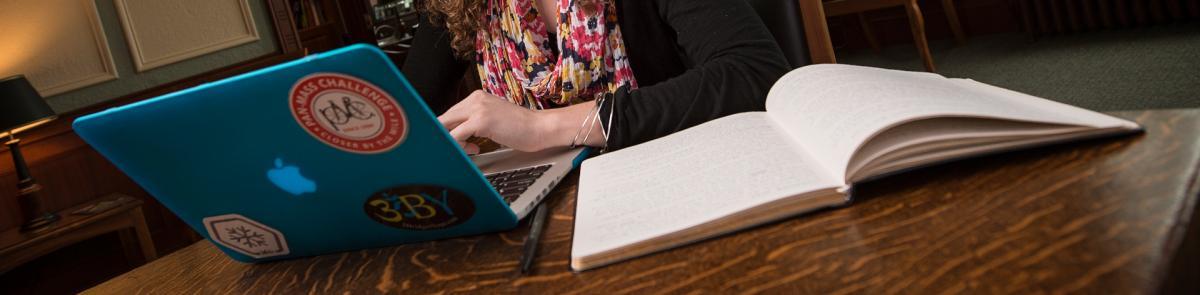 English writing student writing on laptop
