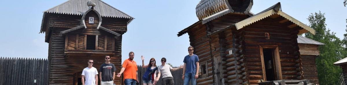 Russian students in front of log cabins