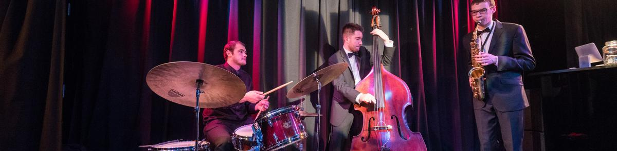 Three students performing in a jazz combo, drum set, bass, and alto saxophone