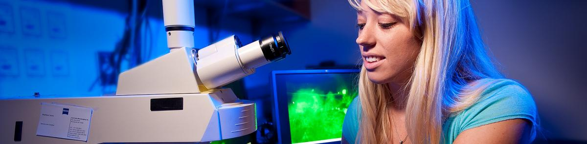 Psychology student in lab with microscope