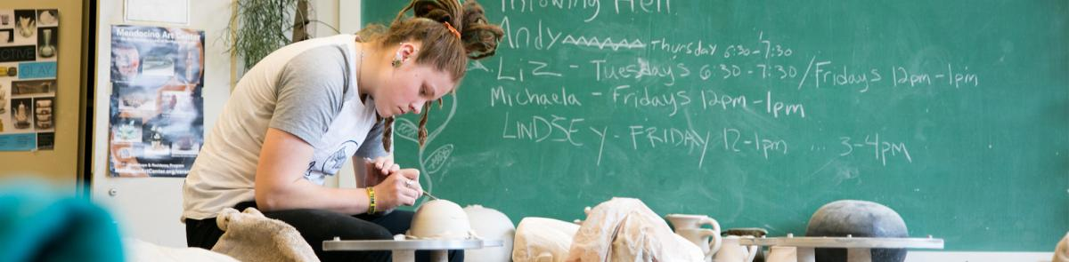 studio art student sculpting with clay