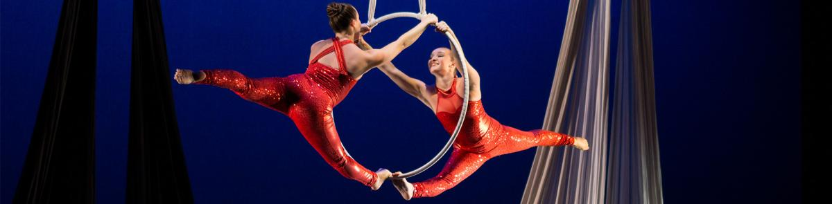 Dance students wearing red, doing aerial dance