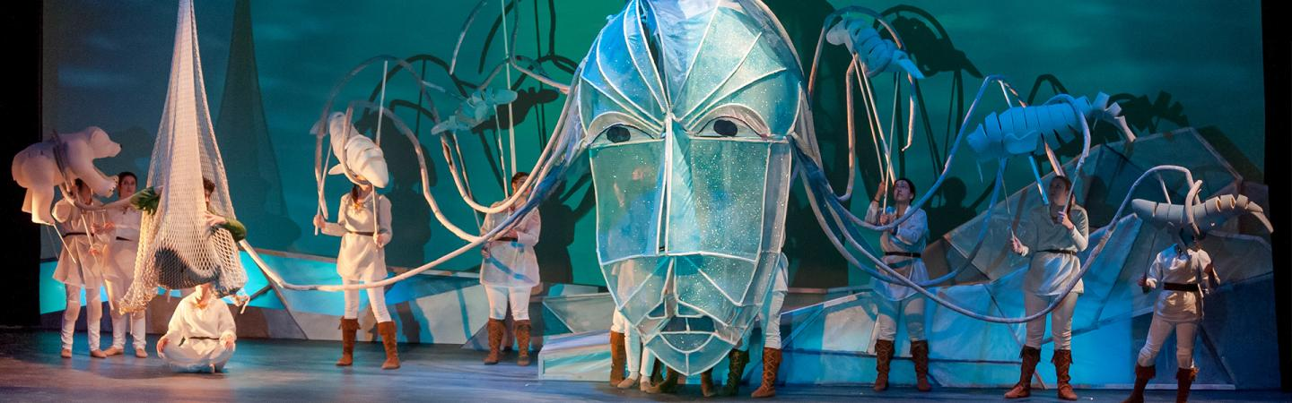 Theater students on stage with a giant mask