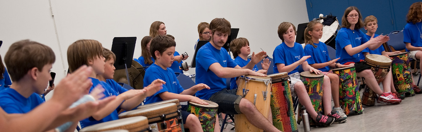 students and teachers playing drums