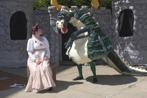 student actors performing with puppets outdoors