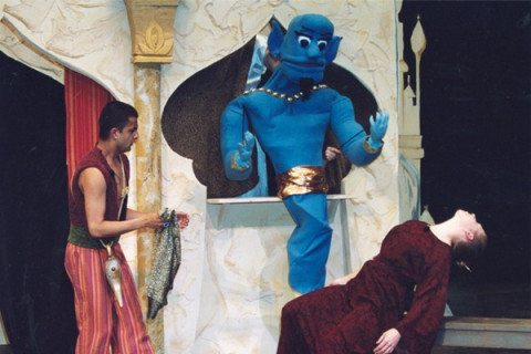 Genie puppet and student actor as Aladdin on stage