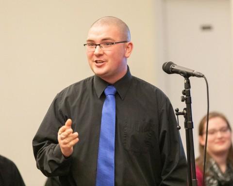man with blue tie singing