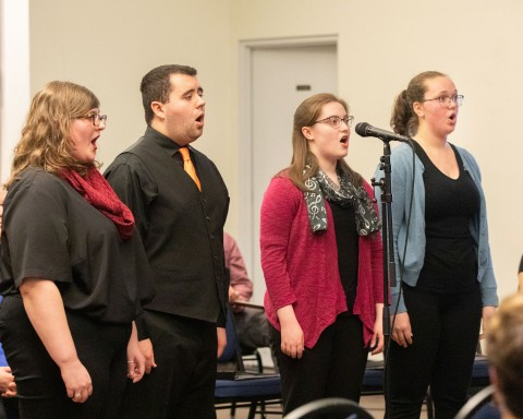 three women and a man singing